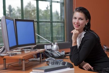 Una atractiva joven empresaria est� sentado frente a un equipo y sonriente. Ella est� descansando su ment�n de su mano. Horizontal a tiros.