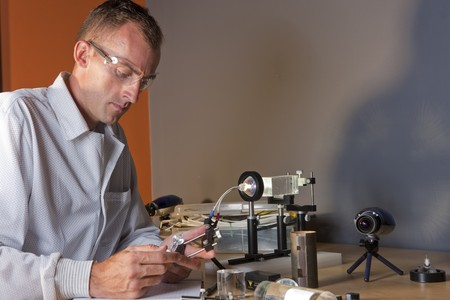A researcher in a lab coat studying a piece of equipment for an experiment. He is wearing safety glasses. Horizontal shot. Stock Photo - 6965437