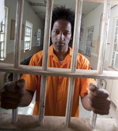 Un hombre africano americano con un afro est� detr�s de una puerta de la prisi�n y es aferr�ndose a las barras. Un disparo vertical.  Foto de archivo