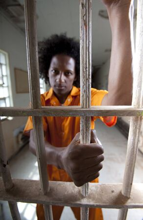 A african american man with an afro is behind a prison gate and holding on to the bars. Vertical shot. Stock Photo