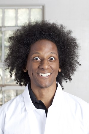 Un joven africano americano con un afro haciendo expresiones faciales mientras llevaba una bata de laboratorio. Un disparo vertical.