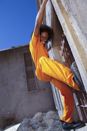 An african american male in orange prison coveralls escaping from prison by climbing a wall. Vertical shot.