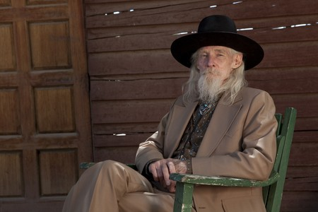 cowboy beard: A senior gentleman wearing a western style suit and cowboy hat is sitting in a chair. Horizontal shot.