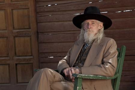 Een senior gentleman, het dragen van een pak van de westerse stijl en cowboy hoed zit in een stoel. Horizont aal schot.