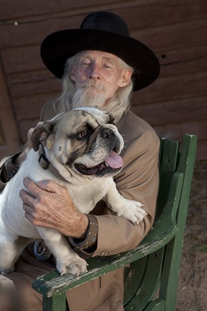 A senior gentleman wearing a western style suit and cowboy hat is sitting in a chair with a bulldog. Vertical shot. photo