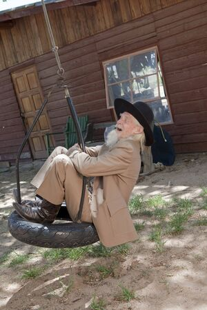 A senior man in a western style suit and hat is laughing and swinging on a tire swing. Vertical shot.