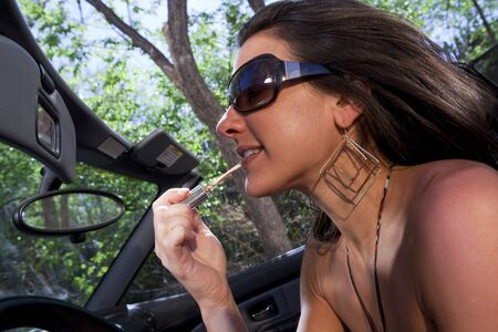 An attractive young woman in a converitble applying lipstick in the rear view mirror while driving. Horizontal shot.
