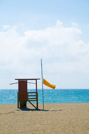 A lifeguard station flying the yellow flag on a Spanish beach