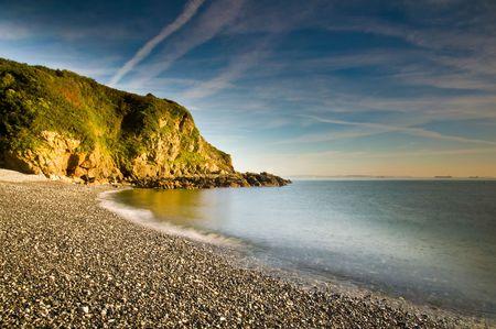 Waves breaking on a shingle beach in Cornwall, UK.
