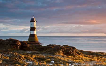 The lighthouse at Black Point on the Welsh coastline bathed in early morning sunlight.
