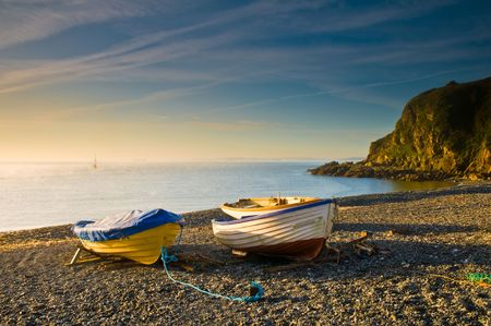moorings: Boats at sunrise on a shingle beach in Cornwall, UK. Stock Photo