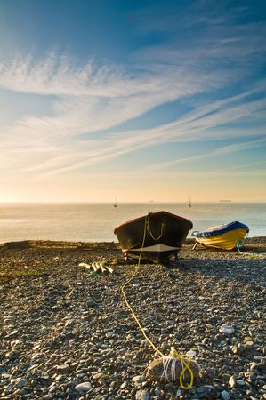 moorings: Two small boats moored up on a shingle beach at sunrise.