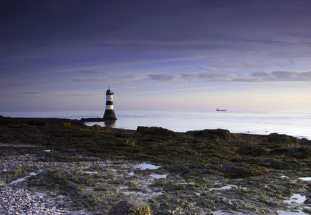 A small lighthouse ensures a safe passage through the waters off the west coast of the UK. Stock Photo