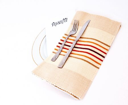 Dinner place setting with a romantic menu isolated against a white background. photo