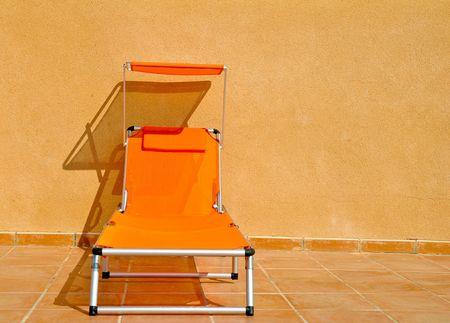 A vivid orange sun lounger on a tiled floor against a buff concrete wall Stock Photo - 4254866
