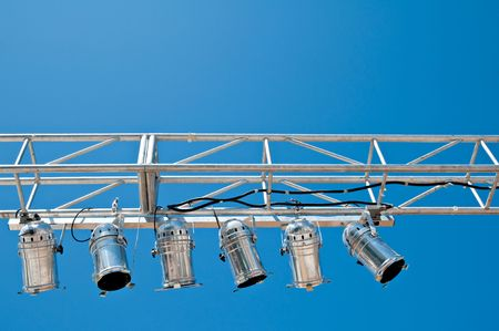 A overhead stage lighting rig against a clear blue sky.