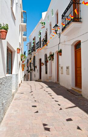 A quiet cobbled street in a small Spanish village.