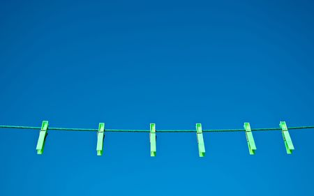 Green clothes pegs on a washing line against a blue sky background.