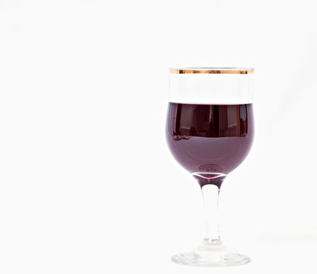 A serving of red wine in a gold rimmed glass.