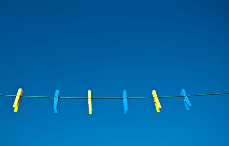 Yellow and blue clothes pegs on a green washing line against a blue sky background.