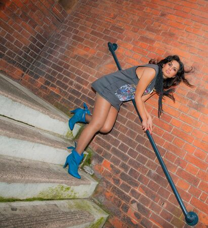 A stunning looking young Asian woman descending the steps in a city centre. photo