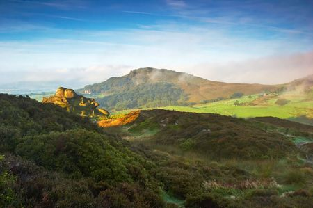 valley below: The early morning sun illuminates Hen Cloud as the remaining mist swirls in the valley below. The Peak District, England, UK. Stock Photo