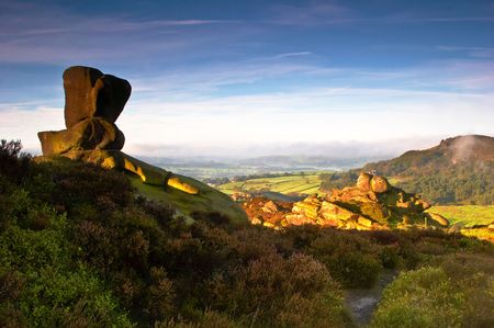 The view from Ramshaw Rocks to Hen Cloud as the sun breaks through on a September morning. The Peak District, England, UK