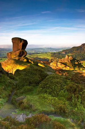 A knuckle stone on Ramshaw Rock in the Peak District, bathed in early morning light. The Peak District, England, UK.