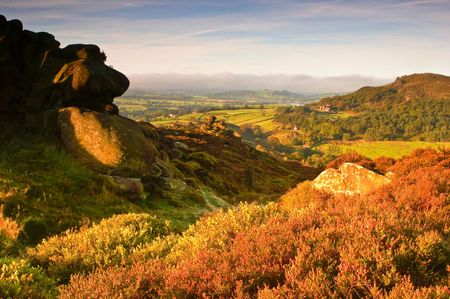 First light illuminates the moorland and pastures of The Peak District in Derbyshire, UK.