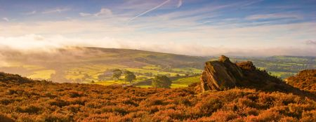 The early morning mist rolls over the heather of The Peak District moorland. Staffordshire, UK. photo