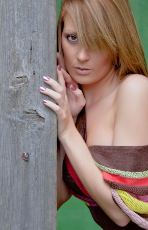 A sexy looking young woman resting against a weathered timber post.