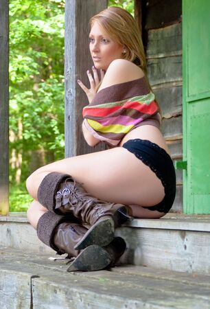A sexy young women sitting on a deck, looking at nothing.