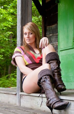 A sexy young woman relaxing on a timber deck.