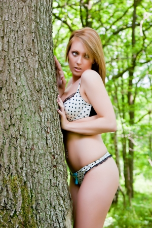 hide and seek: A sexy young woman playing hide & seek with her partner in the forest. Stock Photo
