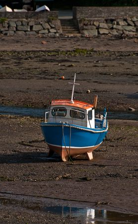 A small fishing boat stranded on the beach at low tide. Stock Photo