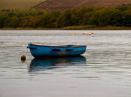 A small blue rowing boat moored in the estuary.