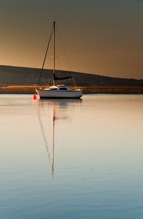 A small sailing boat moored off Borth-Y-Gest in Wales, bathed in dawn light. Stock Photo