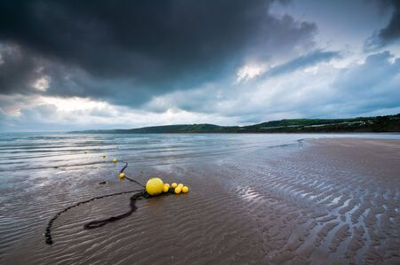 Beach buoys in dawn light at New Quay, West Wales.