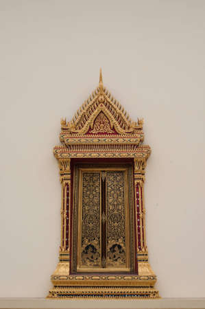 thaiart: The arched window of a thai church which was made by hand using gold leaf, lacquer, colored glass mosaic and brass