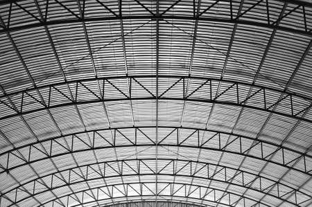 Curved truss high roof suppot within a warehouse Stock Photo