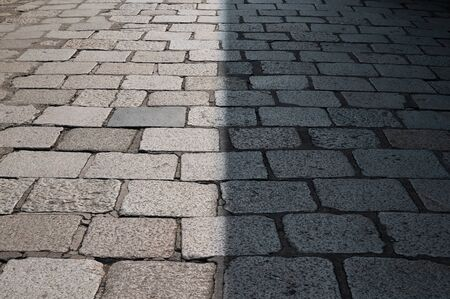 Half shaded century old ancient cobble and granite stone road in Bangkok Thailand