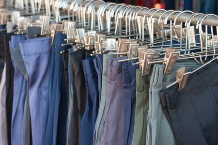 Row of cheap male trousers hanging with hanger selling in a street market