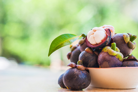 Mangosteen e sezione trasversale che mostra la spessa pelle viola e carne bianca della regina dei friuts, frutto delizioso mangostano disposti su una ciotola, carne di mangostano, primo piano. Mangostano.