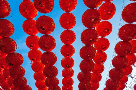 chinatown: Chinese red lanterns hanging in street againt blue sky for decoration during the Chinese New Year festival at Chinatown, Ratchaburi, ThailandChinese Red lanterns illuminated at night Stock Photo