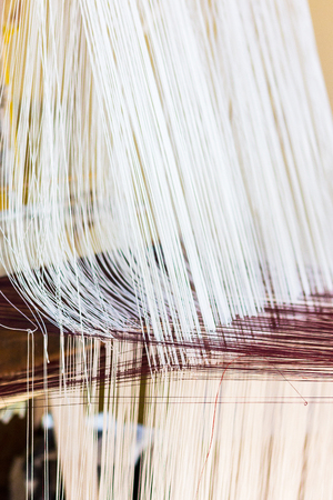 Thread from weaving machine, Abstract background - selective focus.handmade cloth making from thread weave showing the thread pattern of mall line of white and red color cotton thread Stock Photo