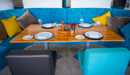 Modern blue dining room, there are chairs and table setup with fancy items.Elegant table set in modern style dining room interior.Nicely decorated and served dining, lunch room table.