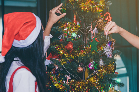 Closeup shot of relatives at home in santa claus costumes, ready to celebrate x mas eve. Happiness, friendship, parenthood, childhood, upbringing, unity, help, mother, father