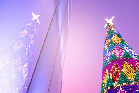 Blurred background of decorated glowing Christmas tree and fireplace.Christmas background with unfocused Christmas tree.Night illumination of Christmas and New Year celebration in colorful pastel.