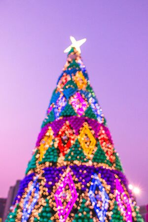 Night illumination of Christmas and New Year celebration in colorful pastel theme.Christmas tree with lights outdoors at night, Bangkok, Thailand
