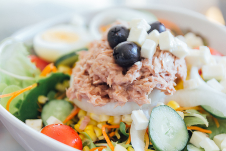 Tuna salad in a bowl with lettuce, eggs, corn, black olives, and tomatoes.Close up homemade fresh tuna salad.